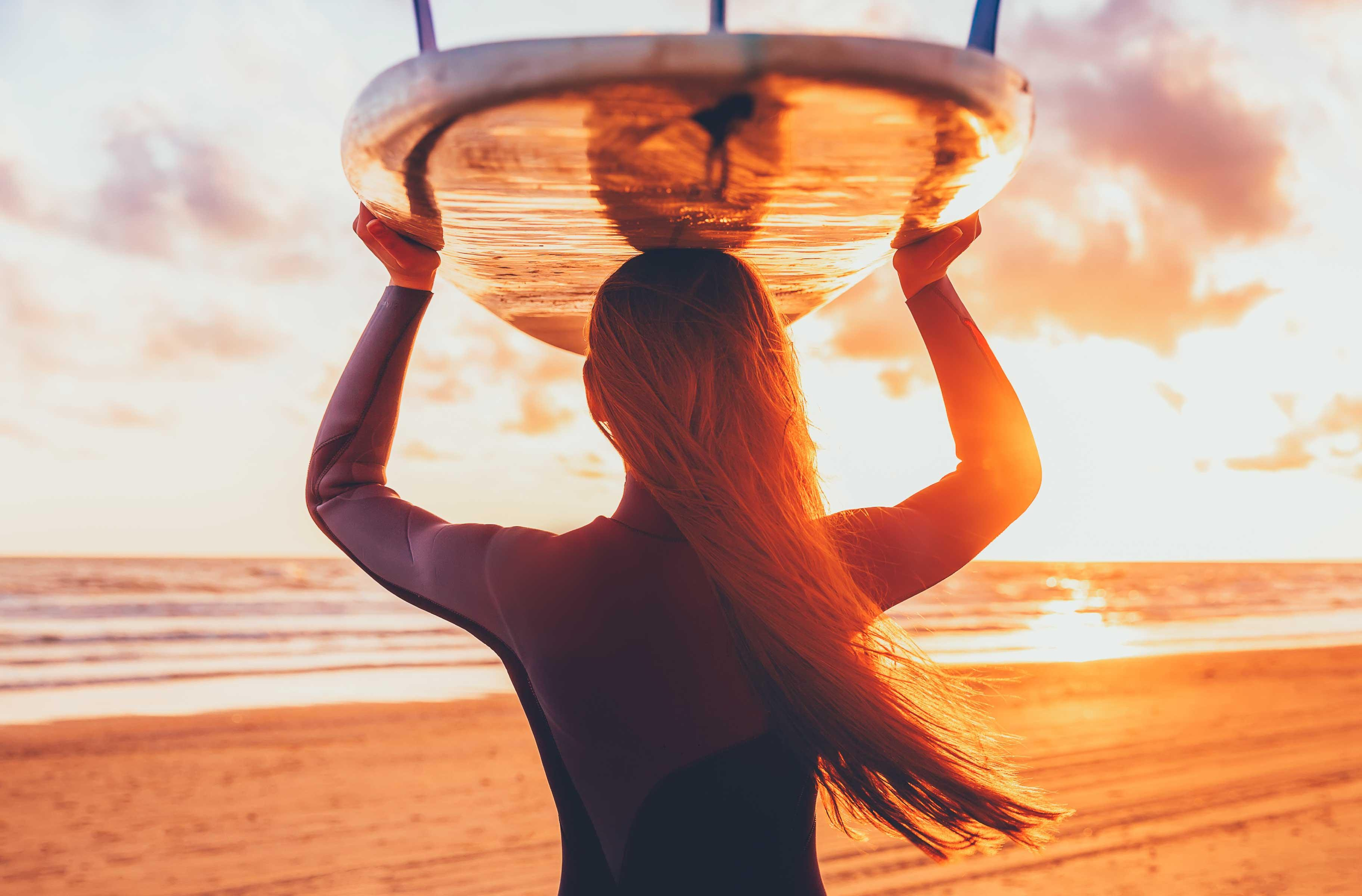 A surfer lady is carrying her surfboard on her head