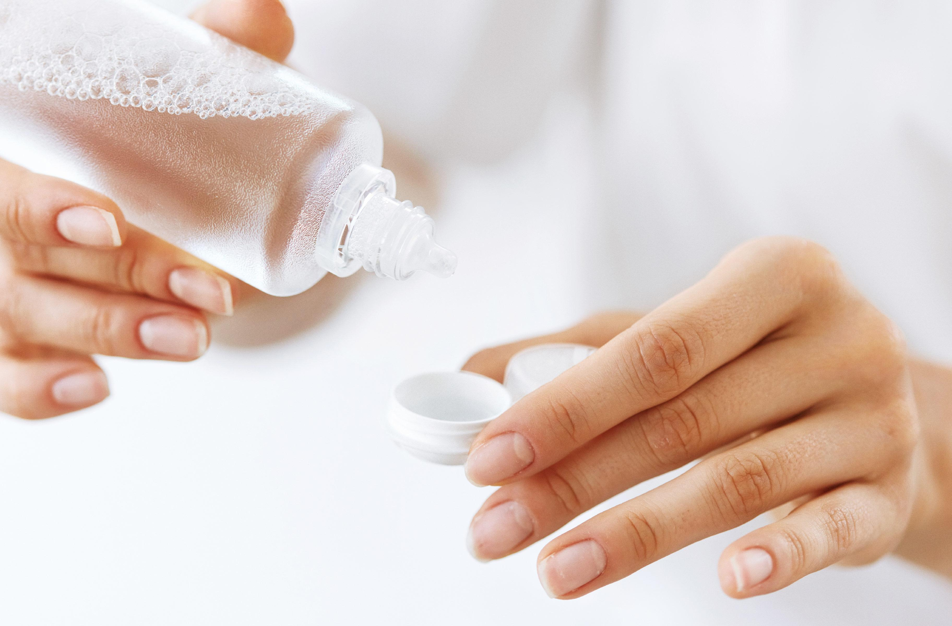 Contact lens solution being poured from a bottle to a case by a woman's hand