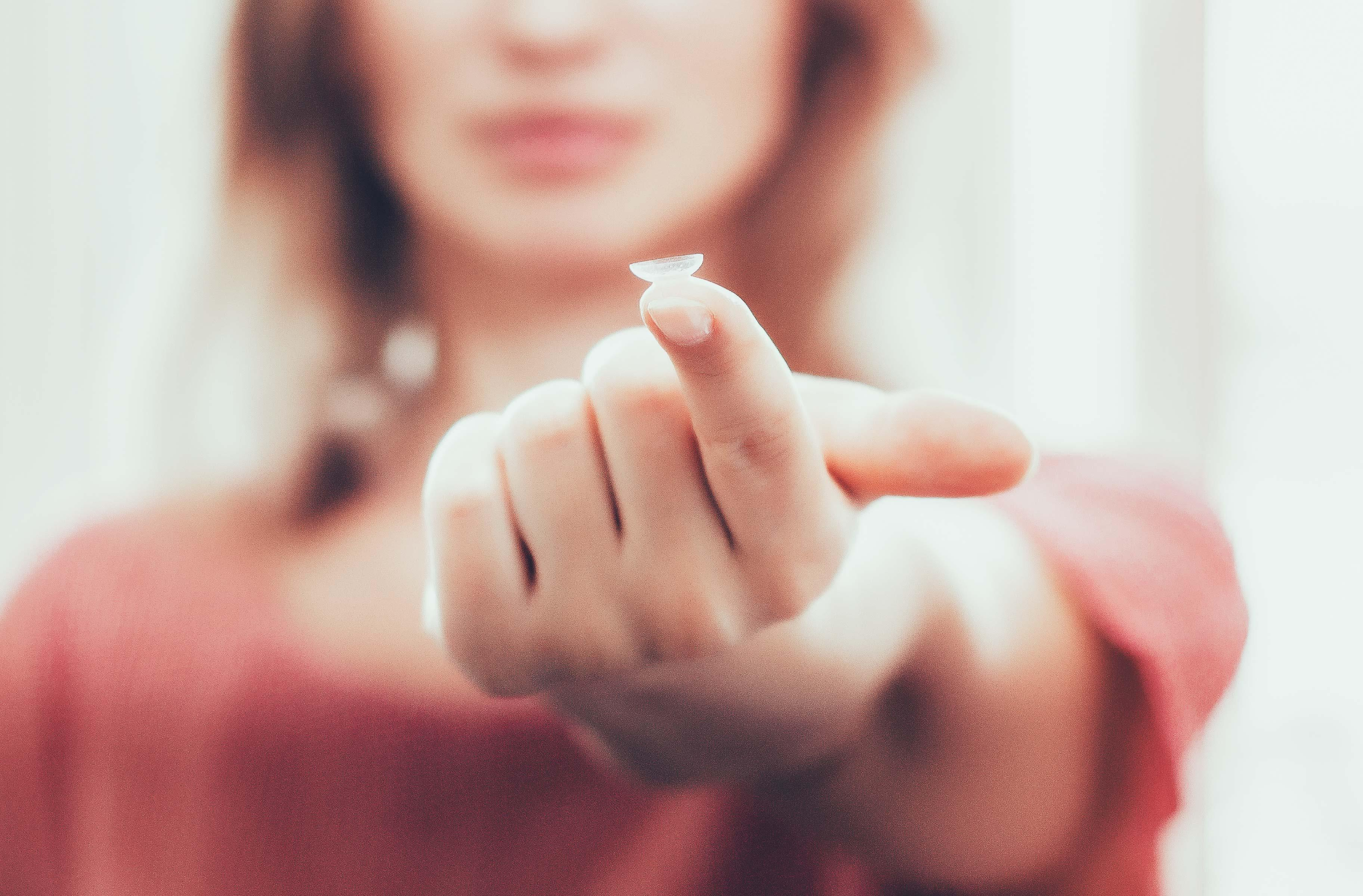 A woman is holding a contact lens on her finger