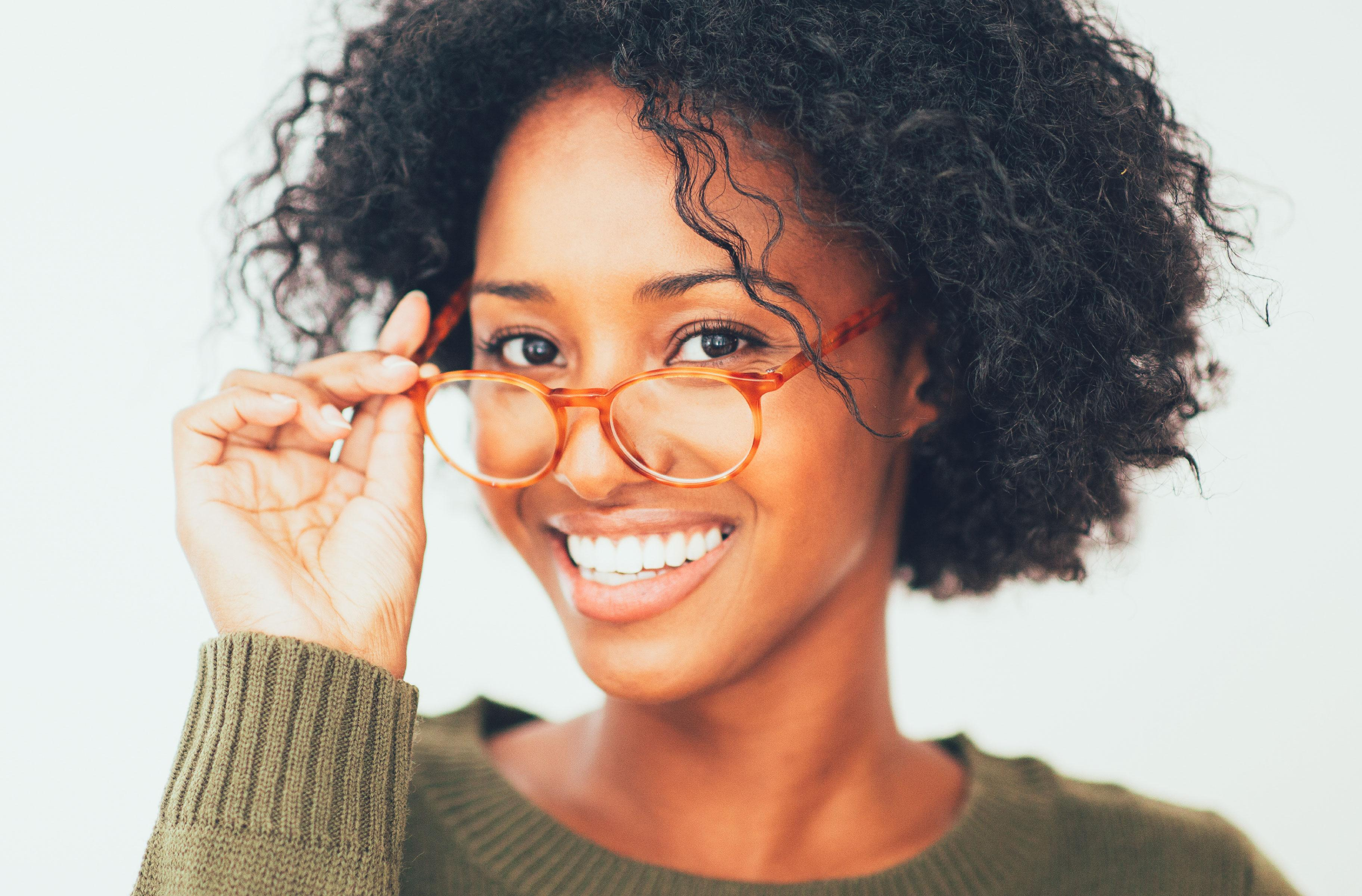 A woman is smiling and holding her glasses