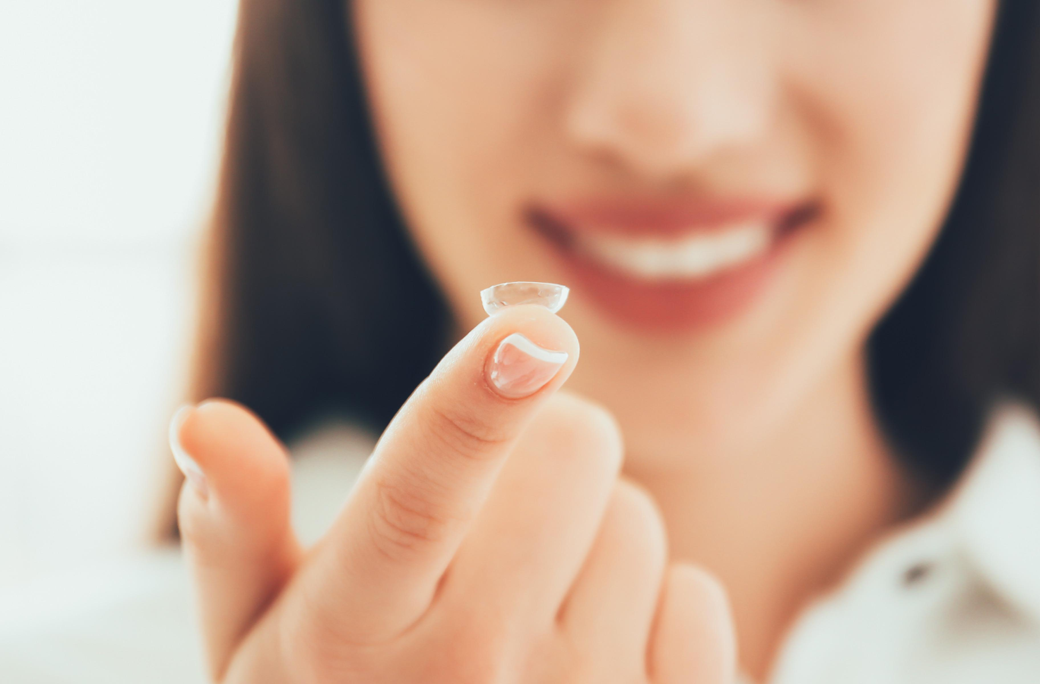 Woman with contact lenses on her finger