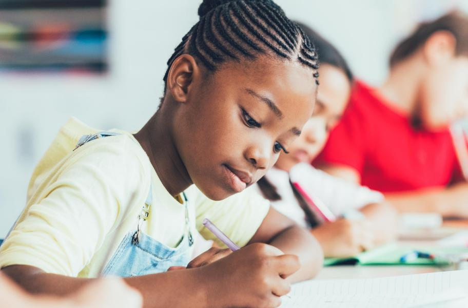 Young girl do her homework in class