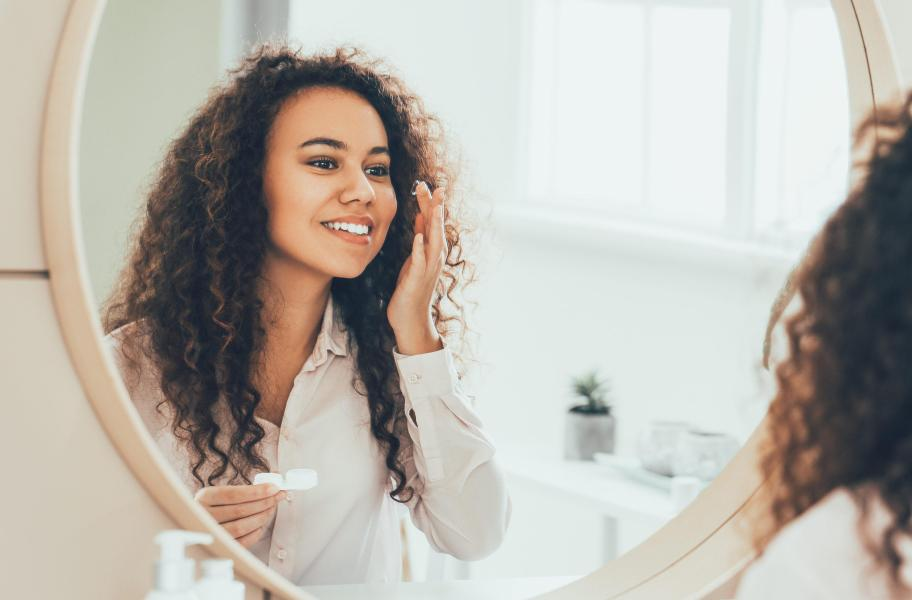 A woman is putting in her contact lenses in front of her bathroom mirror.