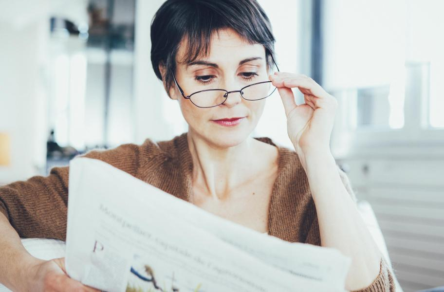A woman is holding her glasses as she's reading the newspaper