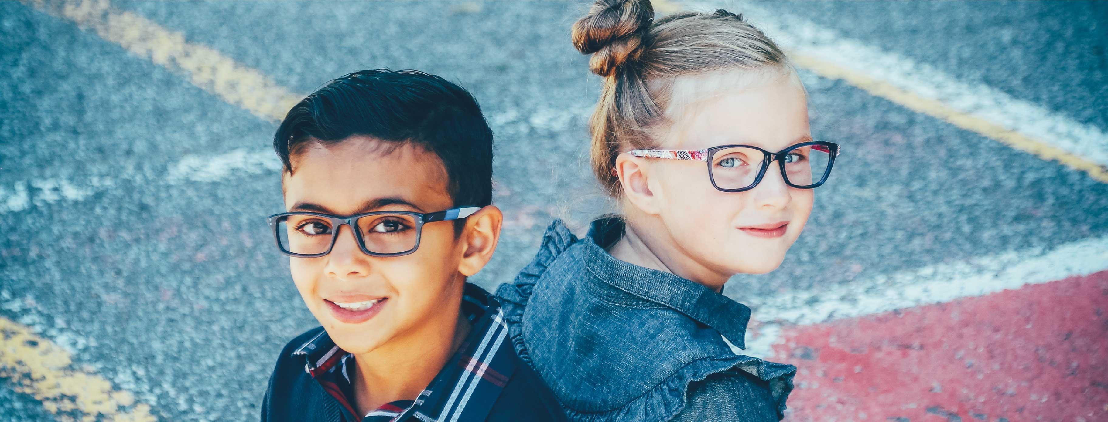 A little boy is alongside a little girl, they both are wearing glasses