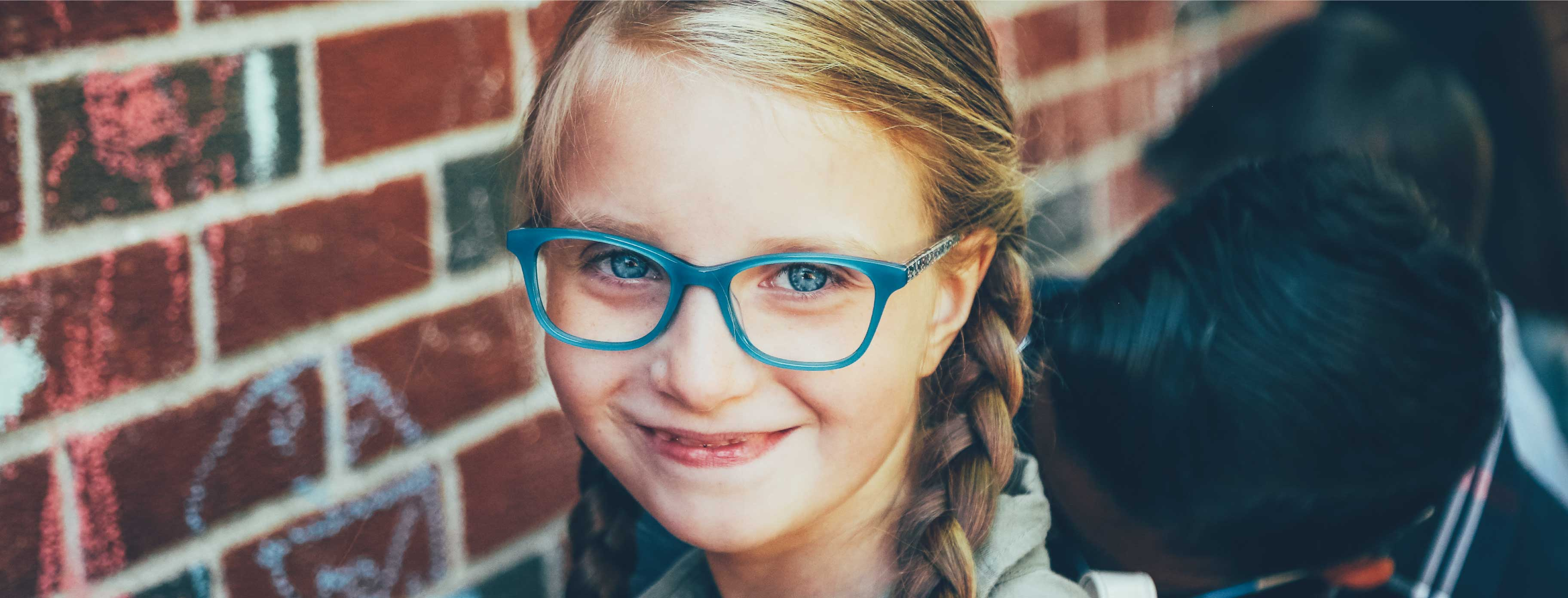 A little girl is in the school yard, she's smiling and wearing glasses