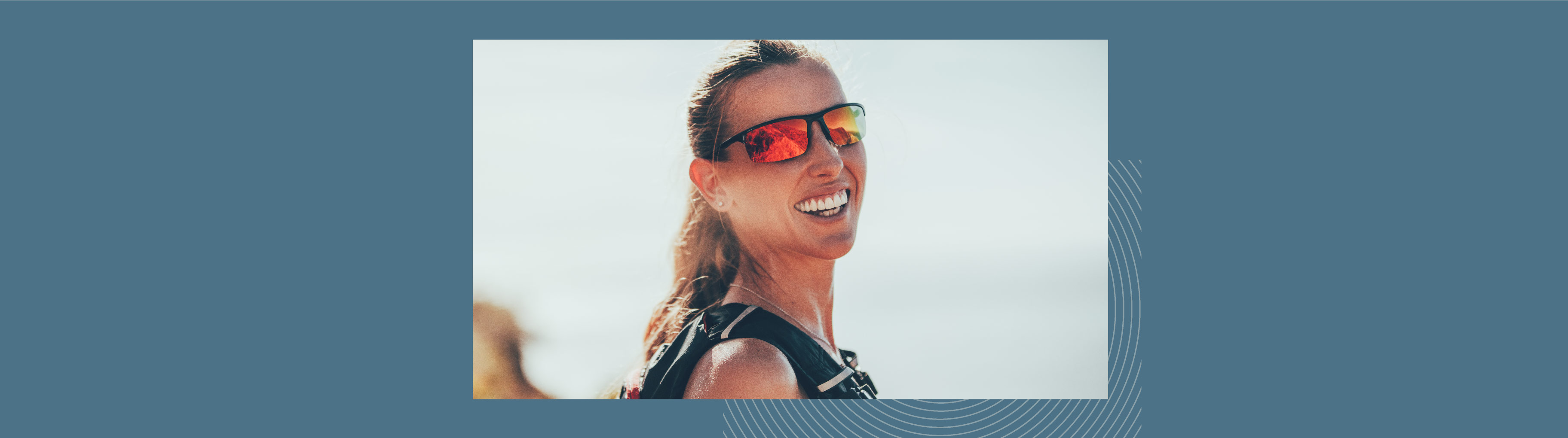 A woman hiking is smiling. She's wearing sunglasses with a red tint that enhance the colours of the panorama.