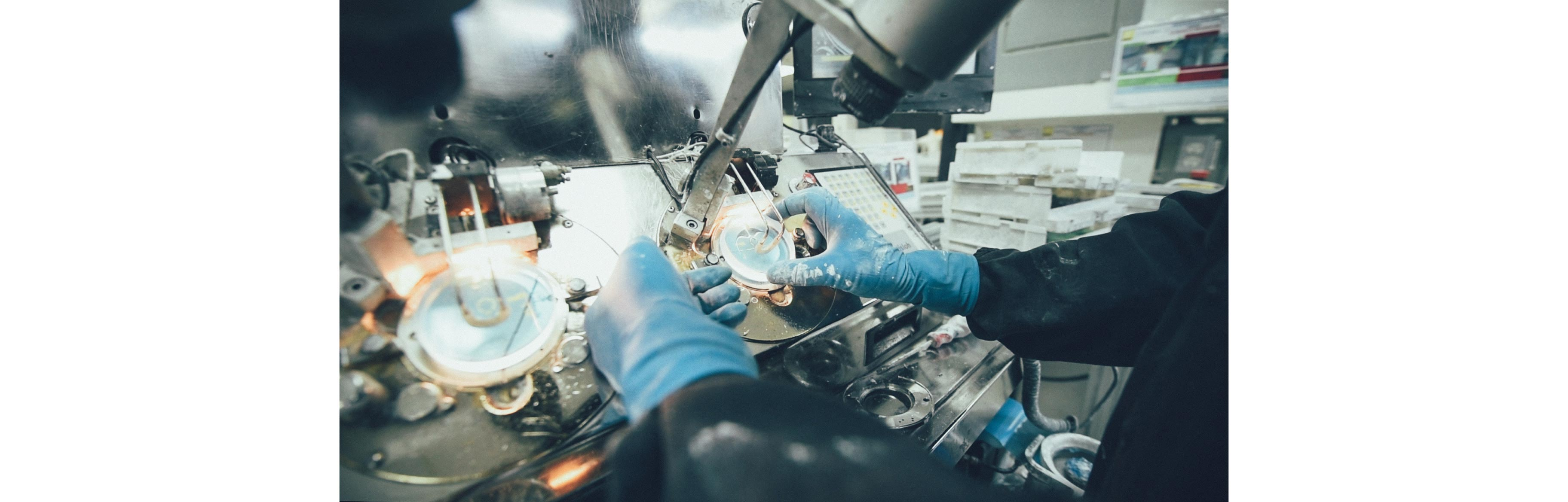 An employee wearing gloves is polishing round ophthalmic lenses using a machine
