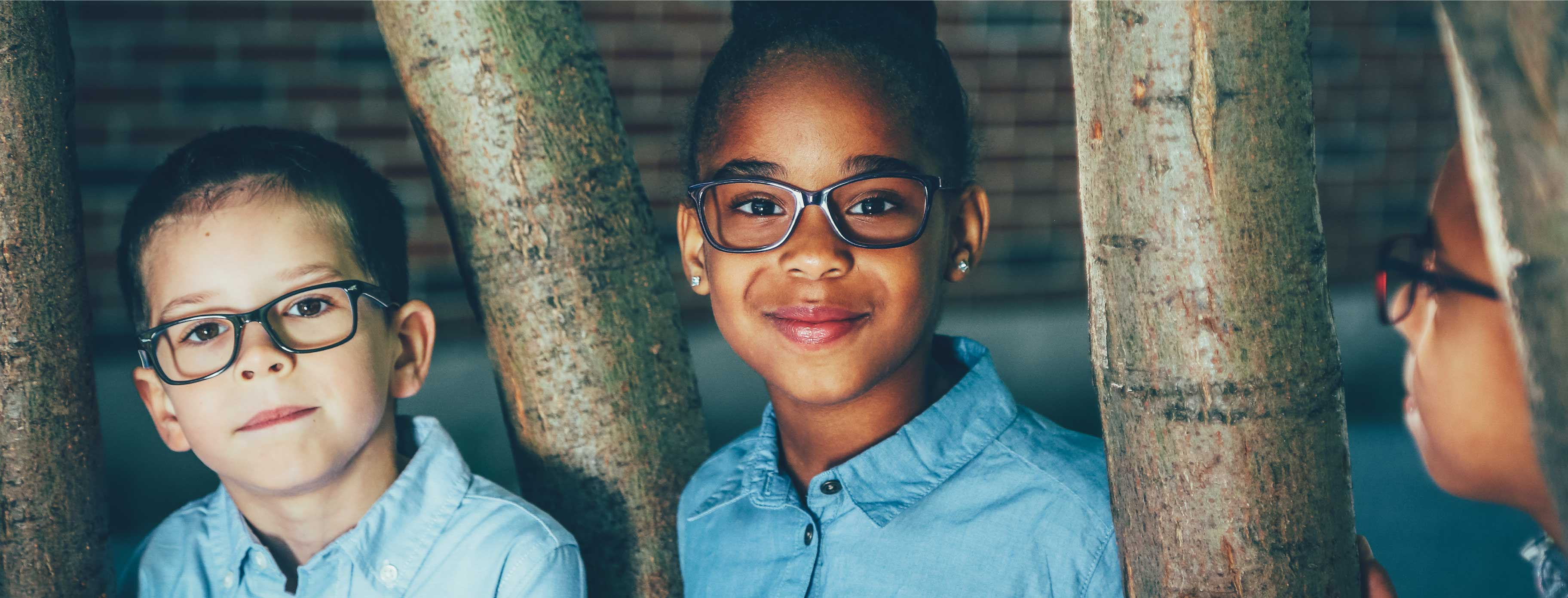 Children are playing outdoors, both of them are smiling and wearing glasses