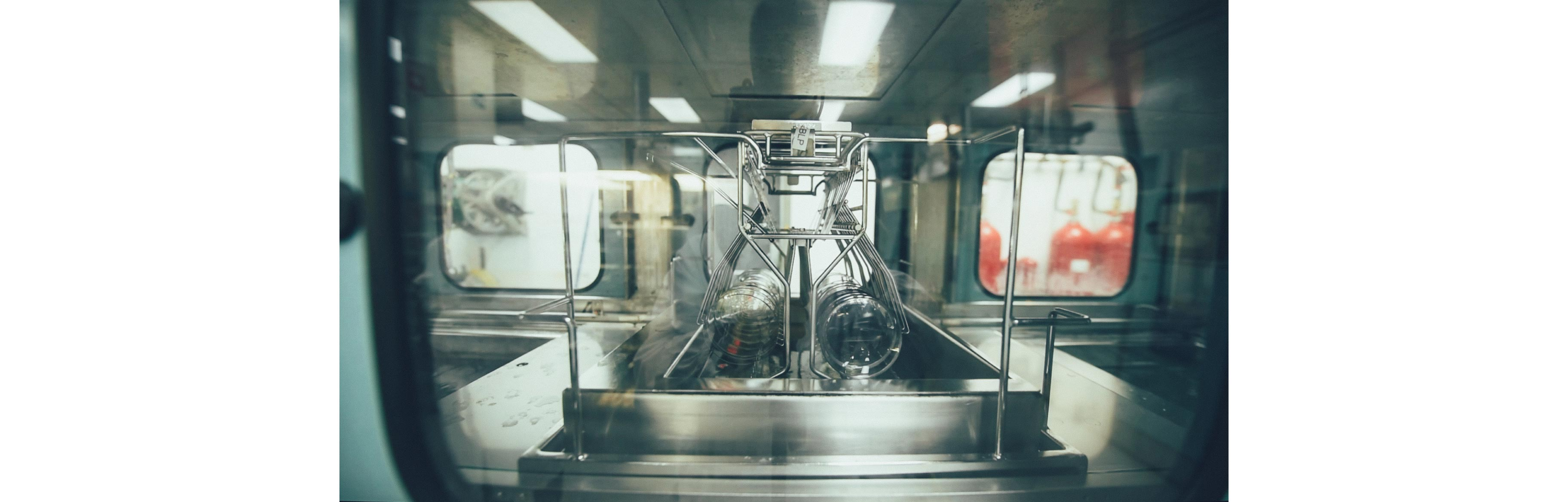 round Nikon lenses are in a machine and being soaked in a chemical solution to coat them according to the patient's needs